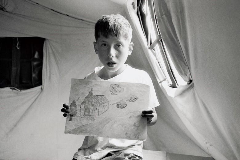 セルビア武装勢力に襲われたラビノト(13)はテントの片隅で、心の傷を癒やそうとするかのように絵を描く(マケドニアの難民キャンプ、1999年)©Yoshino Oishi