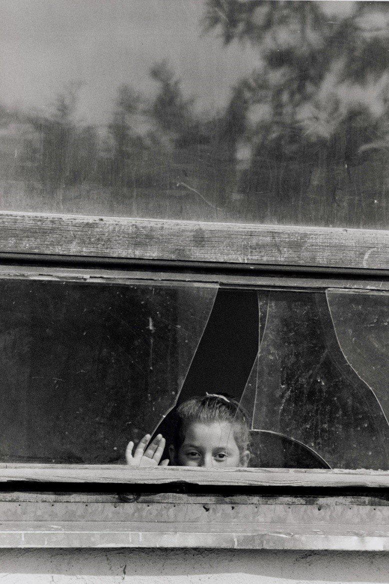 写真・図版 : 壊された校舎の修理はまだまだだ。窓からのぞく少女(コソボ、1999年)©Yoshino Oishi