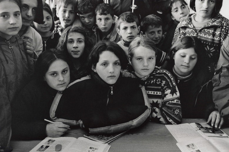 写真・図版 : 級友に囲まれるベサルタ(12、中央)の一家20人は自宅で猛攻撃を受けて、彼女だけが生き残った(コソボ、2000年)©Yoshino Oishi