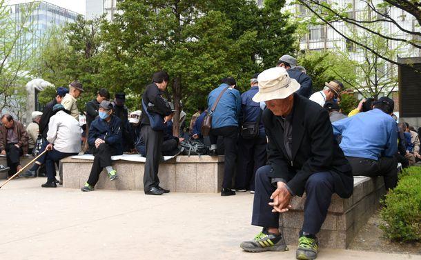 写真・図版 : ソウル市内の広場に集まった高齢者ら。囲碁や将棋を楽しむほか、特に何をするでもなく過ごす人も少なくない=2017年4月