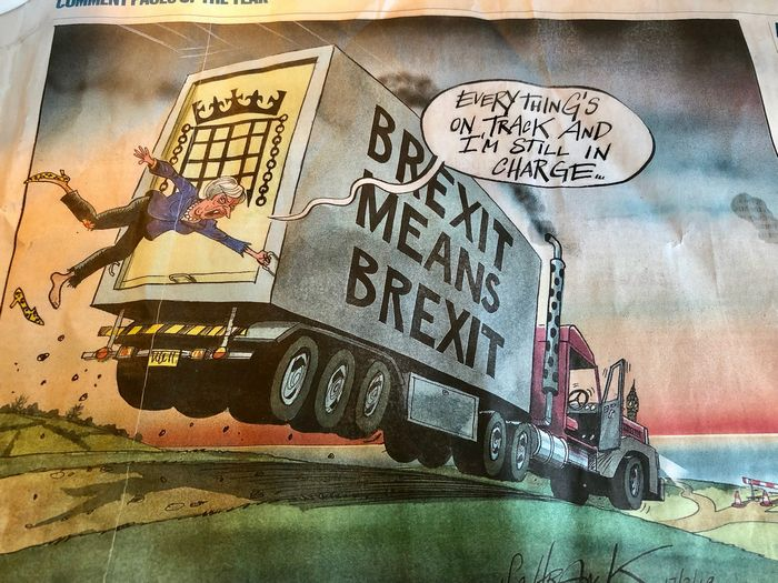 写真・図版 : 「ブレグジットはブレグジット」という文句が書かれたトラックにつかまっているメイ首相。「すべてが予定通りで、私が仕切っている」(サンデー・タイムズ紙、3月17日付、筆者撮影)
