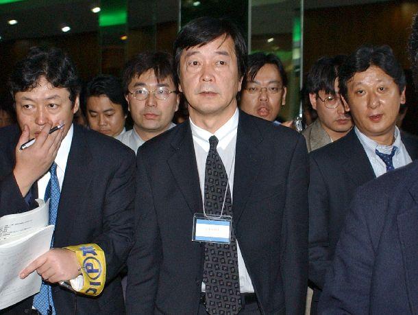 日朝会談後の外務省による記者ブリーフィングのあと、記者団に囲まれ会場を後にする田中均・外務省アジア大洋州局長=2002年9月17日、北朝鮮・平壌市の高麗ホテル