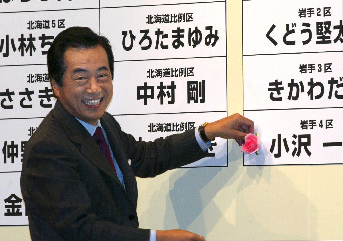 写真・図版 : 2003年衆院選では民主党が躍進。当選を決めた小沢一郎氏の名前に花をつける民主党の菅直人代表=2003年11月9日、東京都港区