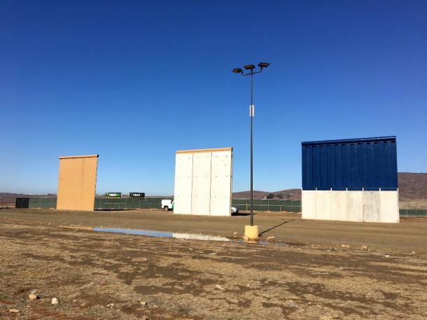 写真・図版 : メキシコ・ティファナの国境の向こうに見える新しい壁の試作品。国境警備隊が白い車を止めて警備していた=2018年11月