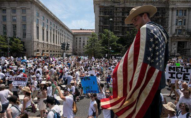 写真・図版 : トランプ米政権の移民政策への抗議活動で、ワシントンのペンシルベニア通りを法務省に向け行進する参加者ら=2018年6月、ランハム裕子撮影