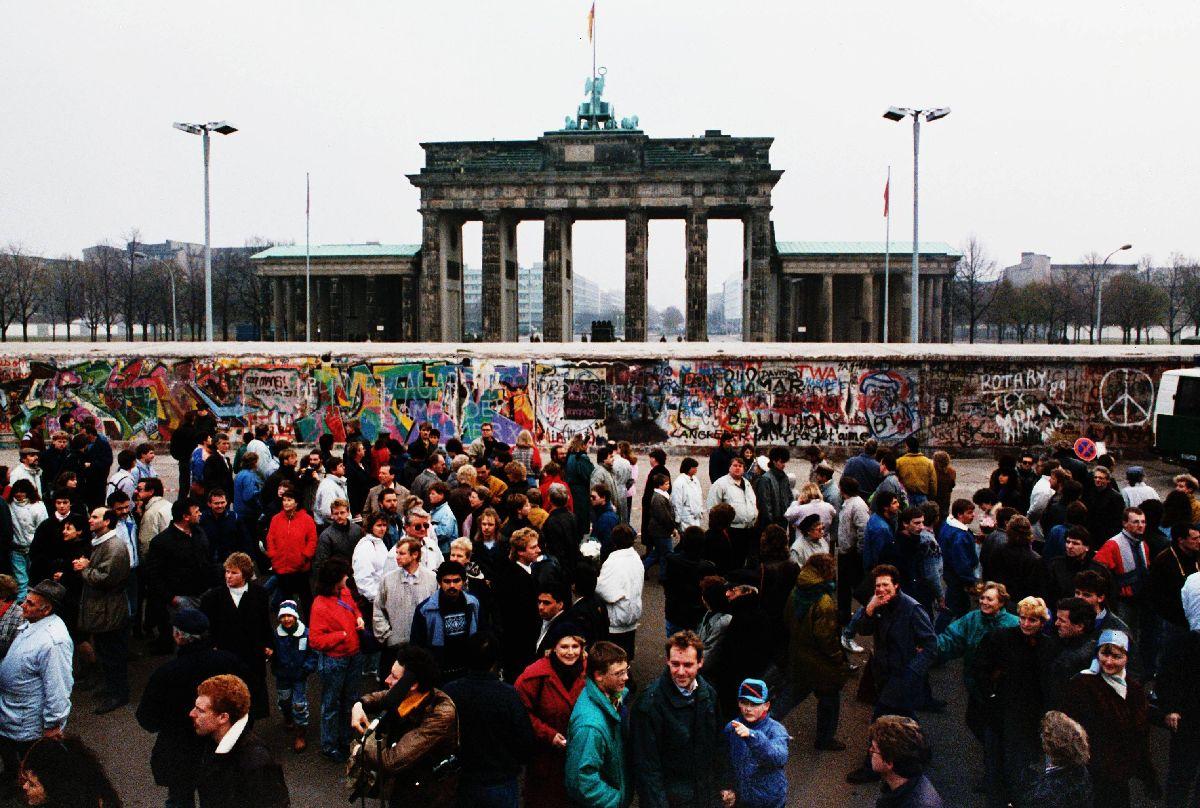写真・図版 : 1989年11月、東西冷戦の終焉を象徴するベルリンの壁が崩壊。写真は、ベルリンの壁解放後初めての日曜日、西側から壁とブランデンブルク門を見ようと集まった東独の市民ら=1989年11月12日