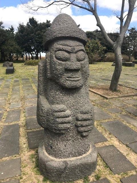 写真・図版 : 済州島特有の守り神「トルハルバン」。「石の爺さん」という意味で、街のあちこちで会える