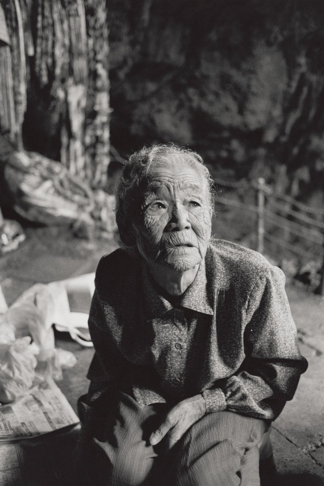 写真・図版 : 佐久本静(1921年生)は、壕のなかで2人目の子を出産したが、そこを追い出されて別の壕に移動した。食糧も水も乏しく、母乳が出なくなり、生まれたての息子は45年6月21日に、3歳の娘は翌日亡くなる(沖縄本島、2005年)©Yoshino Oishi