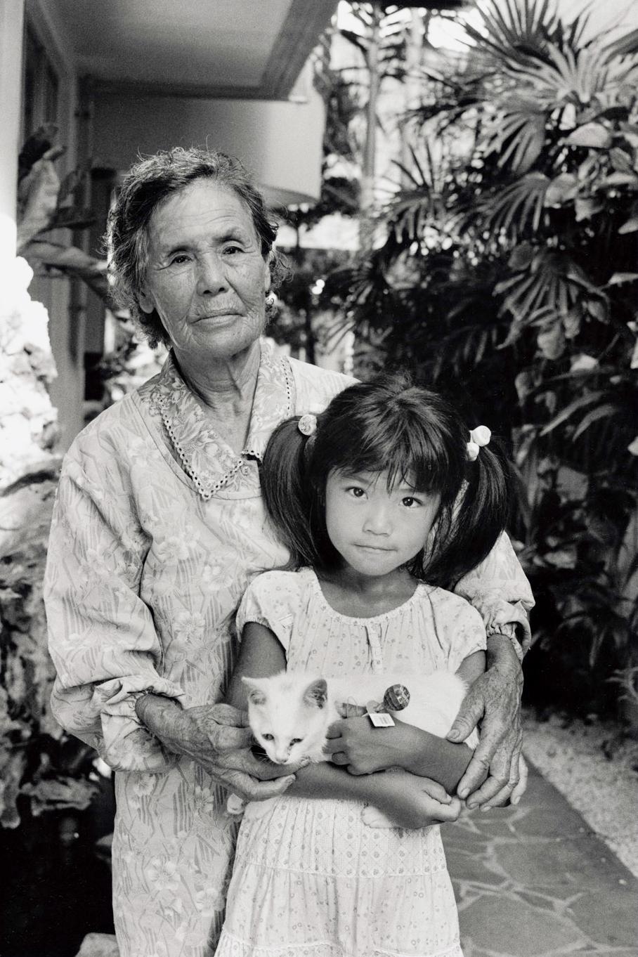 写真・図版 : 宮平春子(1926年生)は、父親から「自決しよう」といわれたが、山に逃げた。兄一家6人、親族の17人、特攻隊で2人の兄が亡くなった。子ども4人、孫7人。孫の愛(6)と里帰りした座間味島で(2007年)©Yoshino Oishi