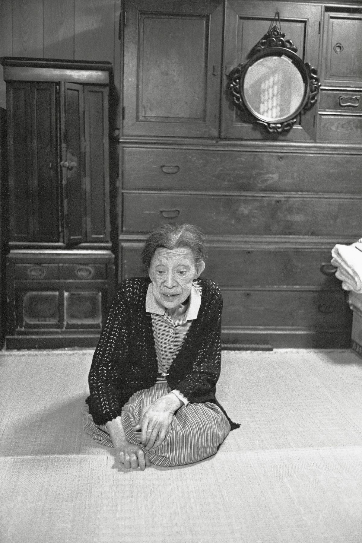 写真・図版 : 清水ツルコ。背後の箪笥は彼女が17歳のときから波乱の人生を見てきた(広島、1994年)©Yoshino Oishi