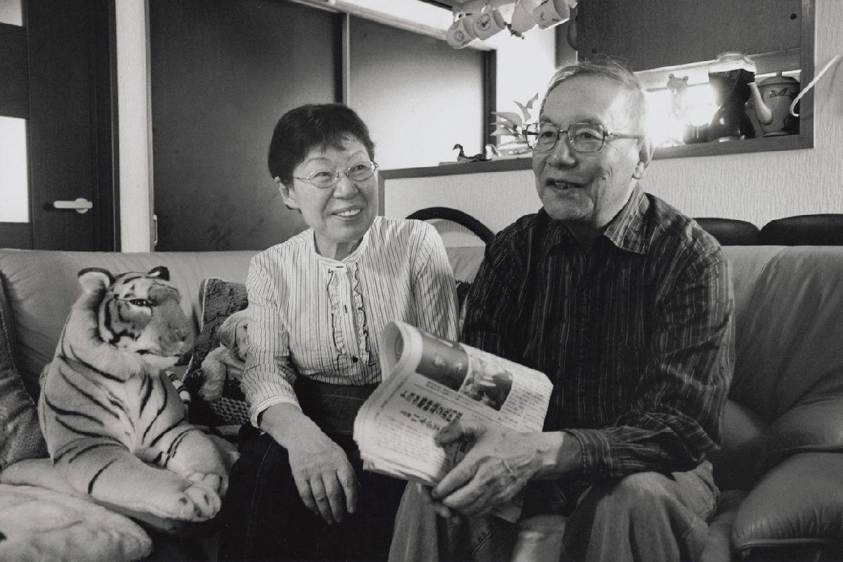 写真・図版 : 山川剛(1936年生)と妻・富佐子(1942年生)。剛は自宅防空壕の脇で熱線を浴びて火傷。小学校の教員になり、平和と戦争を考える教育をつづけた。富佐子は自宅で被爆。小学校給食の栄養士になり、夫と出会う。子ども2人、孫3人。(長崎、2015年)©Yoshino Oishi