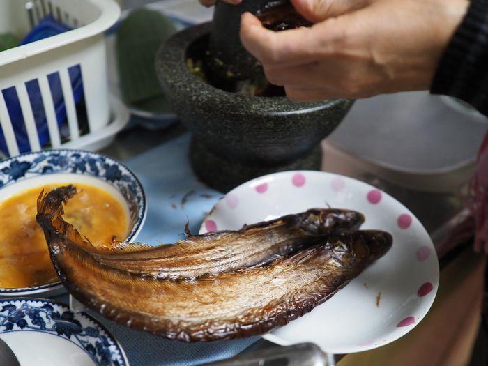 写真・図版 : かちかちに乾燥した干魚も、難なく砕きながら石臼の調味料に加えていく