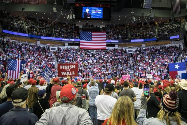 写真・図版 : 「壁を完成させよう」などと訴えるプラカードを掲げ、トランプ集会に参加する支持者ら=2018年10月、米テキサス州ヒューストン、ランハム裕子撮影