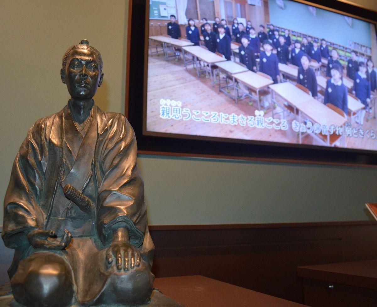 写真・図版 : 吉田松陰の像と、明倫小学校の朗唱教育の様子の展示=1月30日、山口県萩市江向の萩・明倫学舎