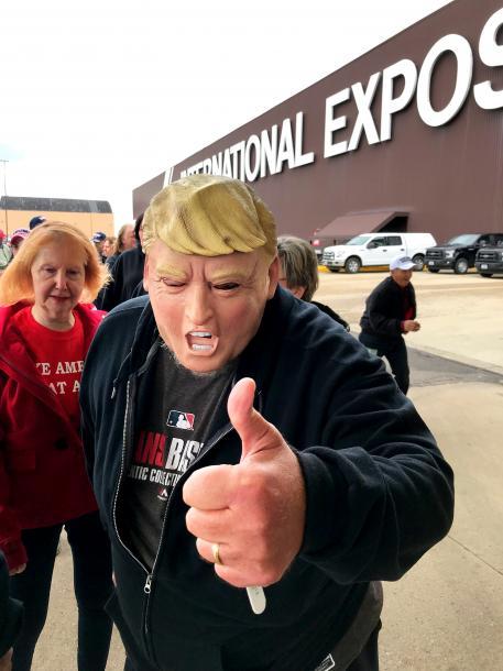 写真・図版 : トランプ米大統領のマスクをかぶった支持者の男性=2018年11月、オハイオ州クリーブランド