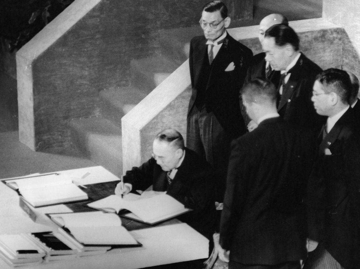 写真・図版 : 1951年9月、米サンフランシスコでの講和条約調印式で日本代表として署名する吉田茂首相=朝日新聞社