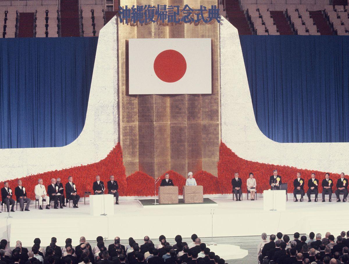 写真・図版 : 1972年5月15日、東京・九段の日本武道館で開かれた沖縄復帰記念式典。壇上中央に天皇・皇后両陛下を迎え、右寄りの演壇で佐藤首相があいさつした=朝日新聞社