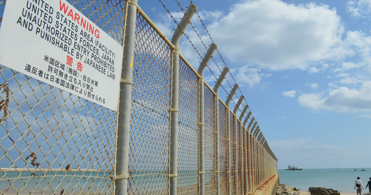 写真・図版 : 沖縄県名護市辺野古。フェンスの向こうの米軍基地の沖で普天間飛行場を移設するための埋め立てが進む=2月下旬。藤田直央撮影