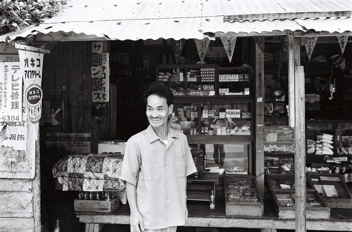 写真・図版 : 1964年、瀬長商店の軒先に立つ瀬長。雑貨や駄菓子を売り、遠くから買いに来るシンパもいたという=那覇市楚辺。朝日新聞社