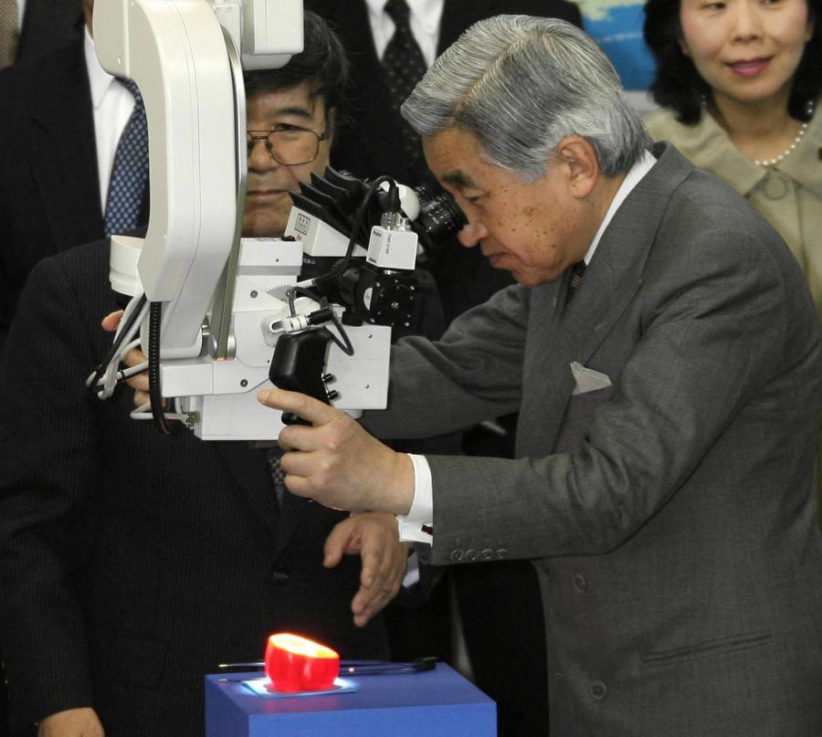 写真・図版 : 三鷹光器を訪れ、手術用顕微鏡でピーマンを観察する天皇陛下= 2006年4月28日