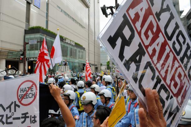 写真・図版 : 警察官に囲まれながら日の丸や旭日旗を手に歩くデモ隊(中央奥)に対し、ヘイトスピーチに反対するプラカードを掲げ、抗議の声を上げる人たち=2016年6月、福岡市