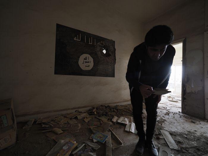 写真・図版 : ISがかつて使っていた部屋の中には「アッラー以外の神はなし」と書かれたロゴがそのまま残されていた