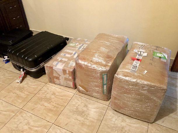 写真・図版 : 赴任する際の荷物。スーツケース1個と段ボール箱3つ。うち一番右側の大きな段ボール箱には、グローブ、ボール、バット、キャッチャーマスクなどの野球道具が詰まっている。