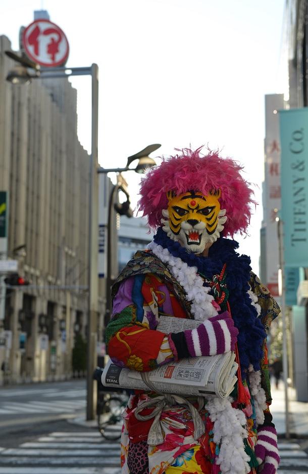 写真・図版 : 早朝の新宿で、配達する新聞を肩から提げて