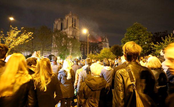 写真・図版 : 燃え続けるノートルダム大聖堂を一目見ようと深夜にもかかわらず、多くの人が周辺に詰めかけた=2019年4月15日、パリ