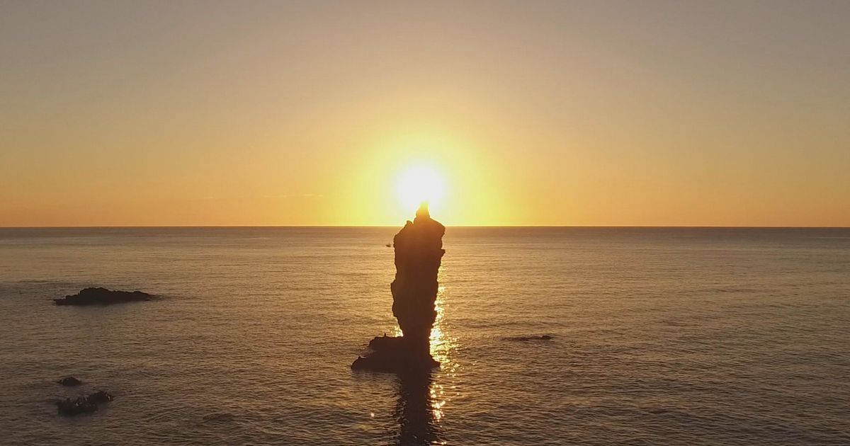写真・図版 : 隠岐諸島の「島後」の沖にあるローソク岩。突き出た岩の先に夕日が重なる=島根県自然環境課提供