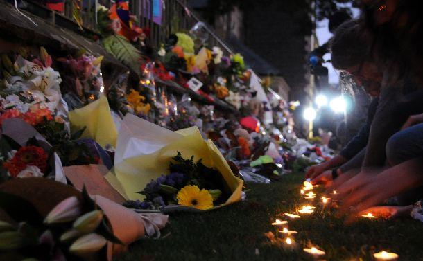 写真・図版 : 銃乱射テロ事件の後、クライストチャーチの公園花やロウソクを捧げる人たちが夜になっても途絶えなかった=2019年3月16日