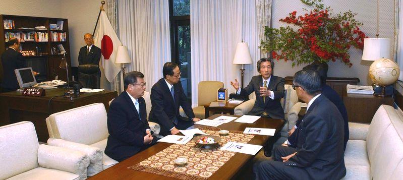 写真・図版 : 旧官邸の首相執務室で福田康夫官房長官らと身ぶりを交え打ち合わせをする小泉純一郎首相。新しい首相官邸が開館するため報道に公開された= 2002年4月26日