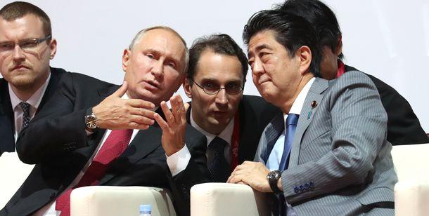 写真・図版 : ロシアのプーチン大統領(手前左)と言葉を交わす安倍晋三首相=2018年9月12日、ロシア・ウラジオストク