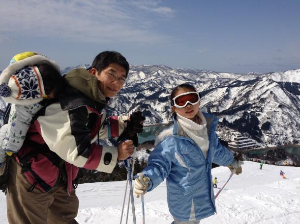 写真・図版 : 石川県出向時代に生まれた2歳の次女を背中におぶりながら10歳の長女とスキー=2013年3月20日撮影、三宅邦明さん提供