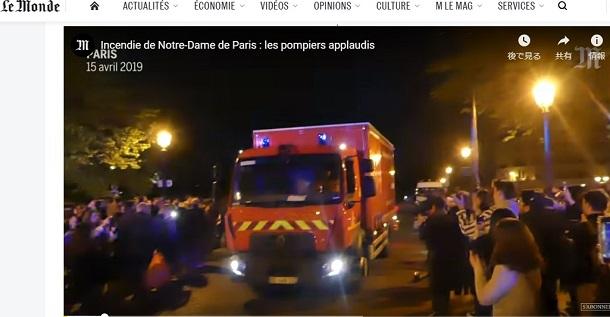 写真・図版 : パリ市民たちが拍手を送るなか、消火活動から戻る消防車=「ル・モンド」のサイトより