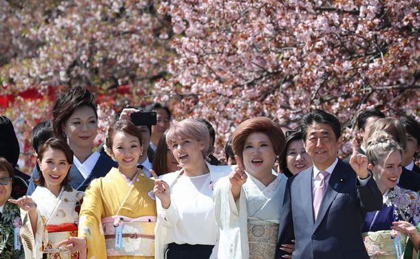写真・図版 : 安倍晋三首相と記念写真を撮る「桜を見る会」の参加者たち=2019年月13日、東京都新宿区