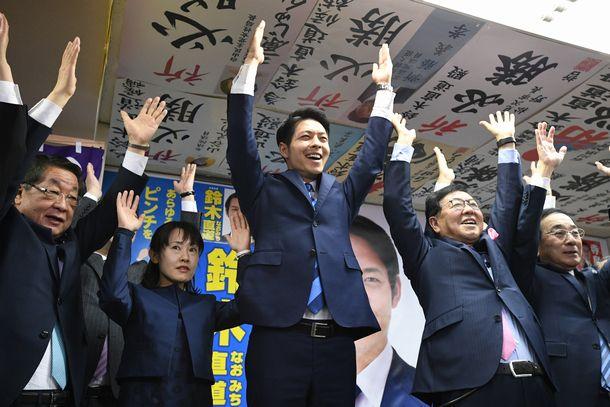 写真・図版 : 北海道知事選で初当選を決め、万歳する鈴木直道氏(中央)=2019年4月7日、札幌市中央区