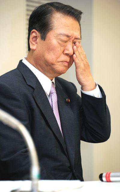 写真・図版 : 初公判後の記者会見の最中に、目を手で押さえる小沢一郎・民主党元代表=2011年10月6日、東京・永田町