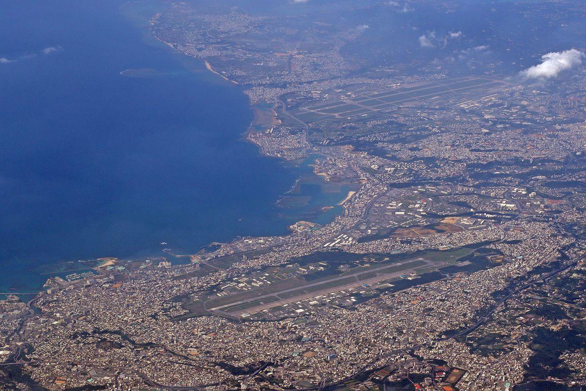 写真・図版 : 市街地に囲まれた米軍の普天間飛行場(手前)と嘉手納基地(奥)=3月。朝日新聞社機から
