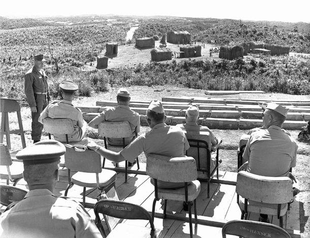 写真・図版 : 住民たちがベトナム人役に仕立てられた『ベトナム村』。左方の畑を米海兵隊が進むのが小さく見える。海兵隊員たちが、村に隠れていたベトコン役の沖縄の住民を捉えて演習終了というシナリオだった。貴賓席のような高台から当時のワトソン高等弁務官ら米軍幹部たちが見学している。=1964年8月26日、沖縄北部訓練場・東村高江(写真・沖縄県公文書館)