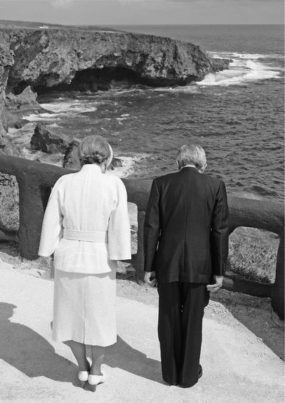 写真・図版 : サイパン島バンザイクリフに向かって深々と黙礼する上皇夫妻=2005年6月28日