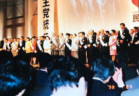 写真・図版 : 民主党結党大会で3カ月後の参院選公認候補が壇上で紹介された。マイクを持つ東京選挙区候補者小川敏夫さんの右、黒いスーツが円=1998年4月27日(筆者提供)