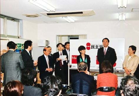 写真・図版 : 四谷に設営した円より子の選挙事務所開きで挨拶をする海江田さん。左から2人目に菅さん、座っている羽田さんの後ろ姿も見える=2004年5月26日(筆者提供)