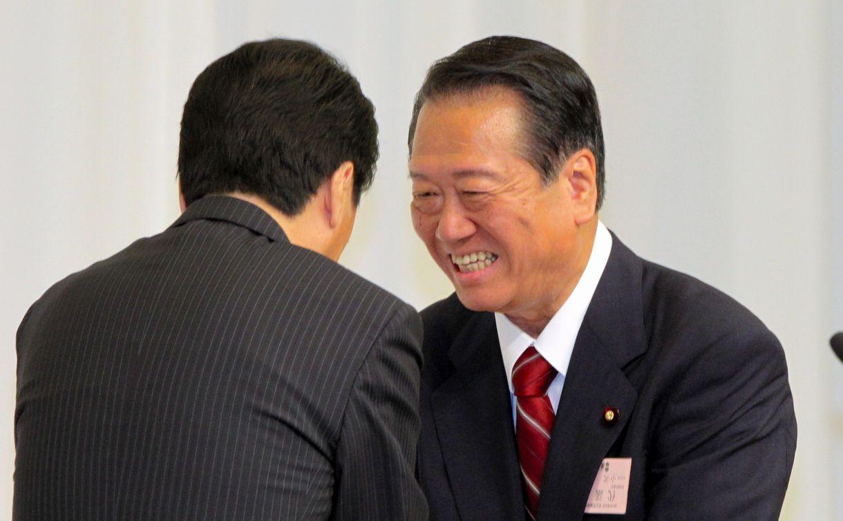 写真・図版 : 民主党代表に再選された菅直人首相(左)と握手する小沢一郎氏=2010年9月14日、東京都港区