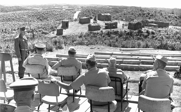 写真・図版 : 高台に設えられた「貴賓席」から演習を見守る米軍将校たち。演習にはベトナム人役として乳幼児などを連れた女性を含む約20人が徴用された。写真左側から海兵隊が一列になって近づいて来るのが見える。最終的にベトコン役の二人が捉えられて演習は終わった。1964年8月26日、東村・高江(写真・沖縄県公文書館)
