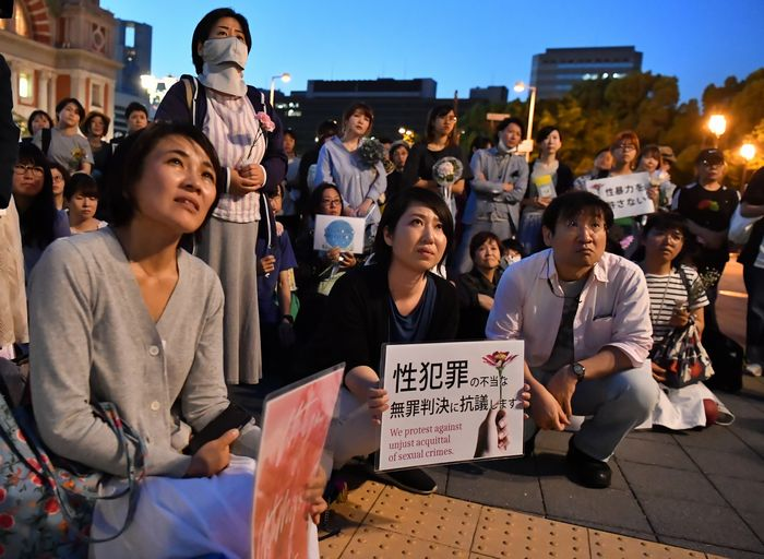 写真・図版 : 花やプラカードを手に、性犯罪や性暴力の無罪判決に抗議するフラワーデモの参加者たち=2019年5月11日、大阪市北区