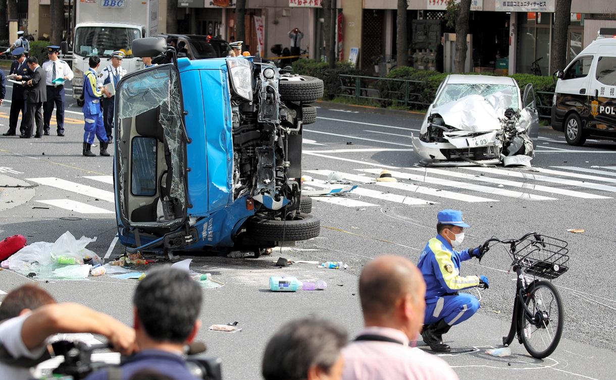 通行人を次々とはねて大破した乗用車(右)と、交差点で衝突されて横転したごみ収集車の周辺を調べる捜査員=2019年4月19日午後2時7分、東京都豊島区東池袋4丁目