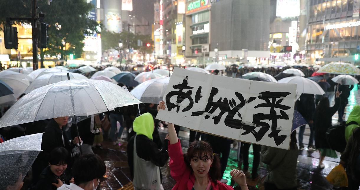 平成最後の日、渋谷スクランブル交差点の前で、ボードを掲げる女性=2019年4月30日