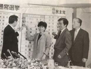 写真・図版 : 参院選投開票日の夜、民主党本部で羽田孜さん、菅直人さん、山花貞夫さんと一緒に当選の花を自分の名前につけた円= 1998年7月12日