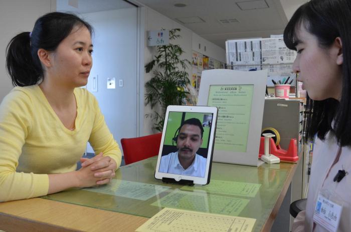 写真・図版 : 外国人居住者に向けた行政の多言語対応は目の前の課題。写真はタブレット端末を使った「テレビ電話通訳」=2018年4月、愛知県